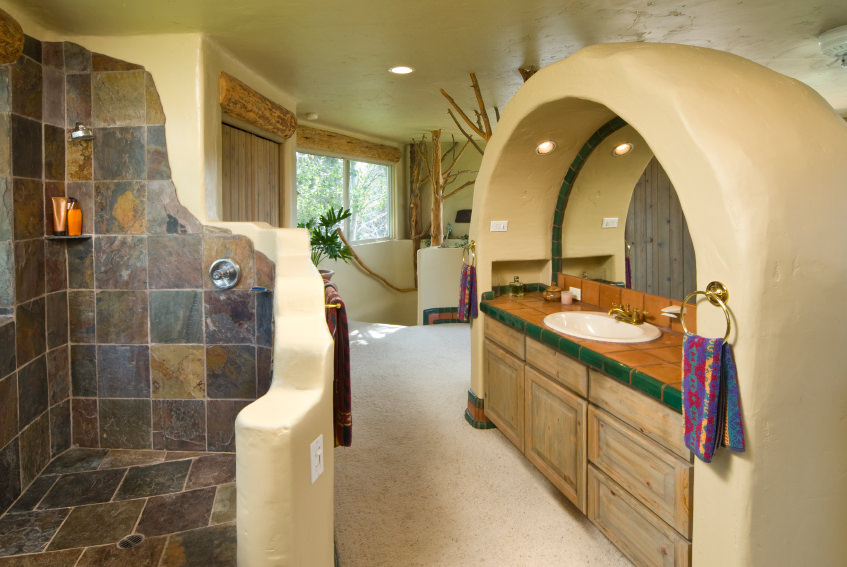 Master bathroom boasting a custom walk-in shower and a fancy sink counter design. The room has carpeted floors and beige walls.