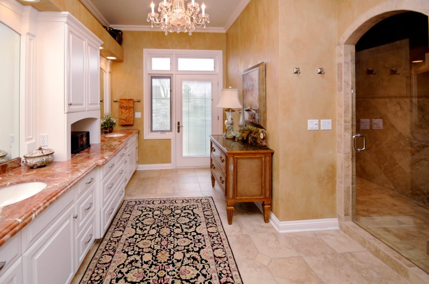 Large master bathroom featuring tiles flooring and beige walls. The room offers a gorgeous sink counter and a large walk-in shower room, together with a fancy chandelier light.