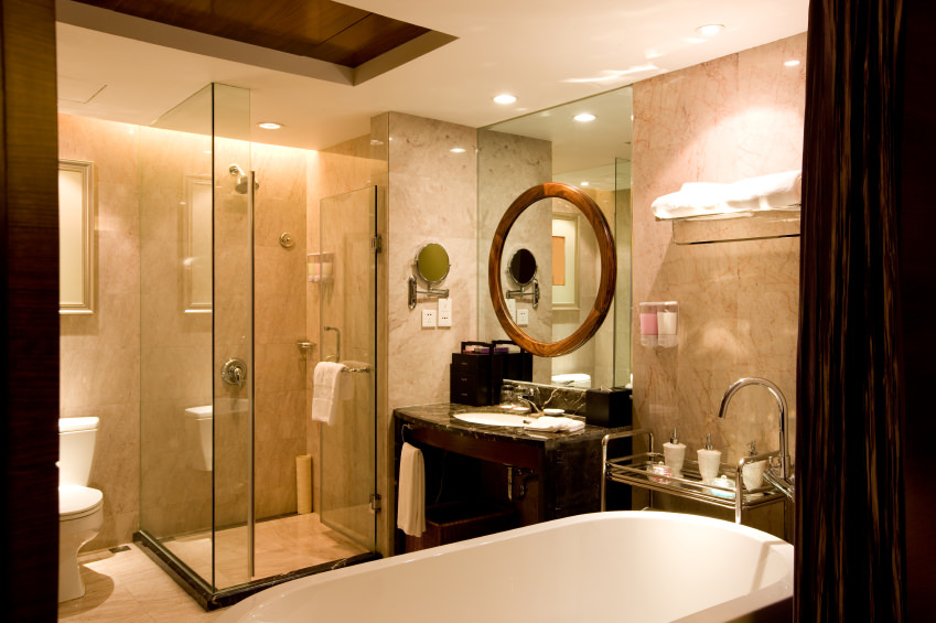 Master bathroom boasting a walk-in shower, a large freestanding tub and a single granite sink counter.