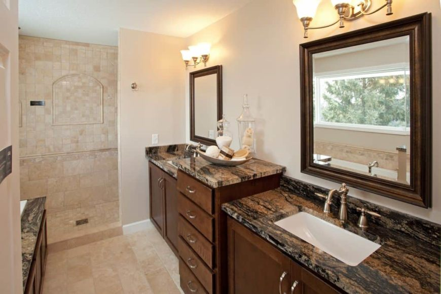 A close up look at this primary bathroom's gorgeous sink counters lighted by classy wall lights. The room offers a walk-in shower area.