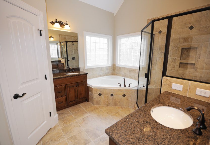 Master bathroom featuring a corner drop-in tub, a corner walk-in shower and two granite sink counters lighted by wall lights.