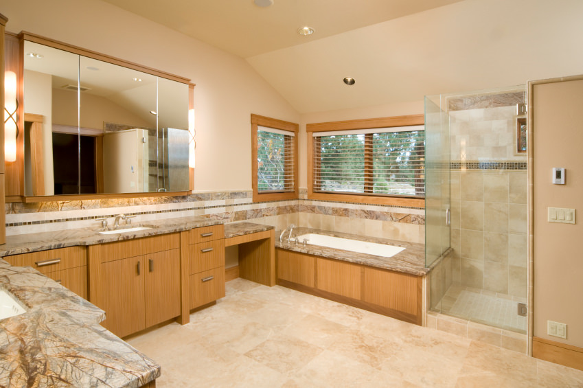 Master bathroom with beige tiles flooring. The room has stunning sink counters and a drop-in tub platform, along with a corner shower.