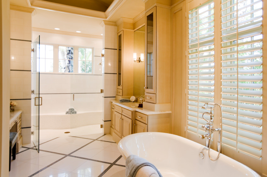 Master bathroom with beautiful tiles flooring and beige walls. The room offers a sink counter, a powder desk, a freestanding tub and a walk-in shower room.