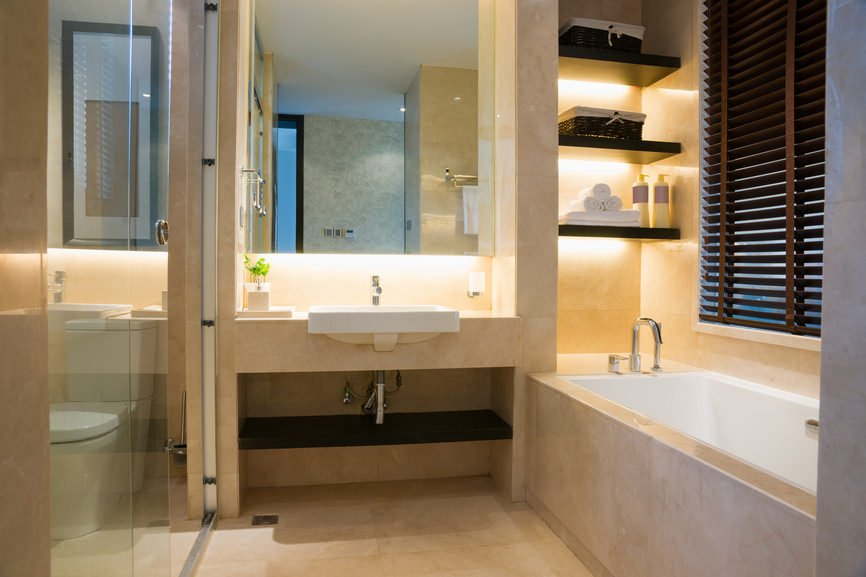 Master bathroom with a built-in sink in between the toilet room and the drop-in deep soaking tub by the window.