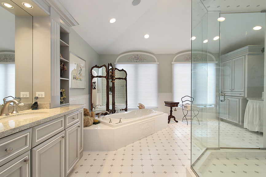 Large master bathroom with classy tiles flooring. It offers a gorgeous drop-in soaking tub and a large walk-in shower, along with a marble sink counter.