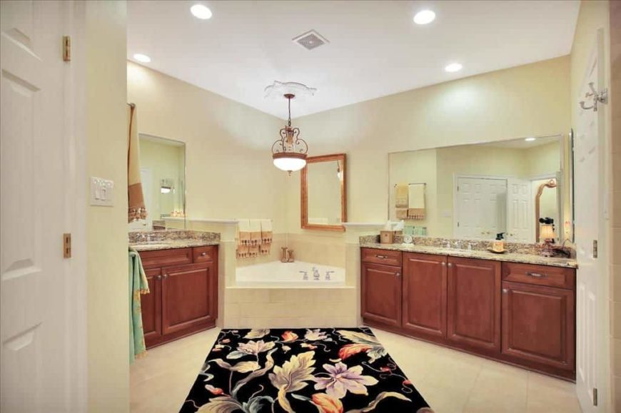 Primary bathroom with a drop-in corner tub and two sink counters with granite countertops. The tiles flooring is topped by a stylish area rug.