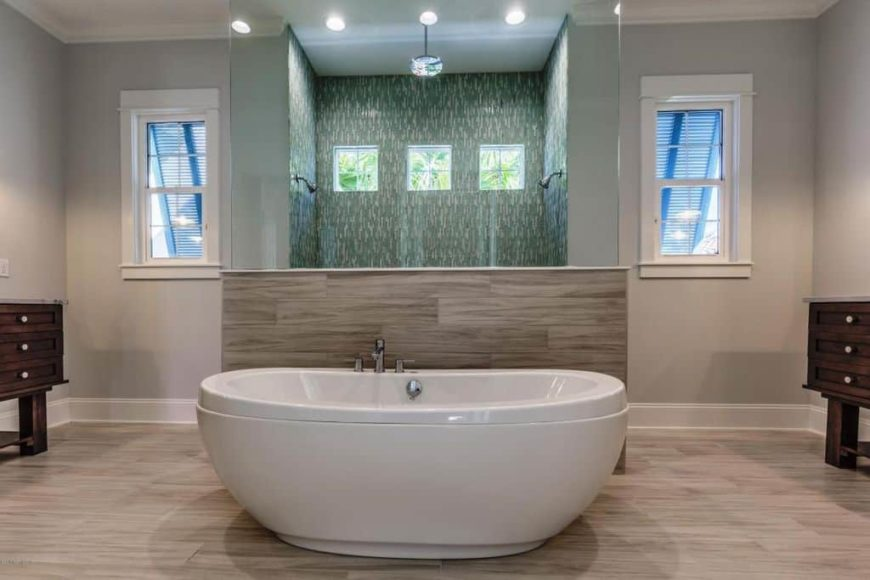 A focused shot at this primary bathroom's large freestanding tub set on the hardwood flooring. The room also offers a walk-in shower with stylish walls.