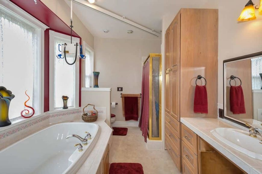 A narrow primary bathroom featuring a rustic reach-in closet, along with a walk-in shower, a deep soaking tub and a sink counter lighted by a classy wall light.