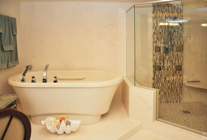 This primary bathroom features beige tiles walls and floors. The room offers a deep soaking freestanding tub and a walk-in corner shower room.
