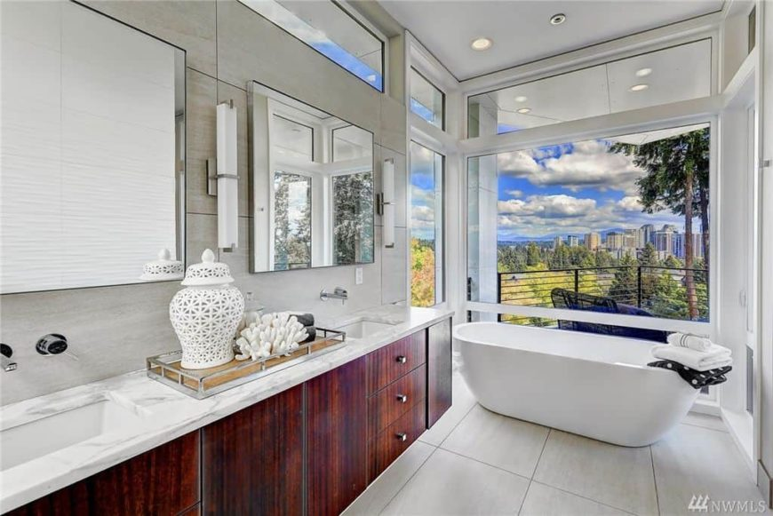 Primary bathroom with tiles flooring and glass windows overlooking the stunning outdoor views. The room also has a freestanding deep soaking tub by the windows.