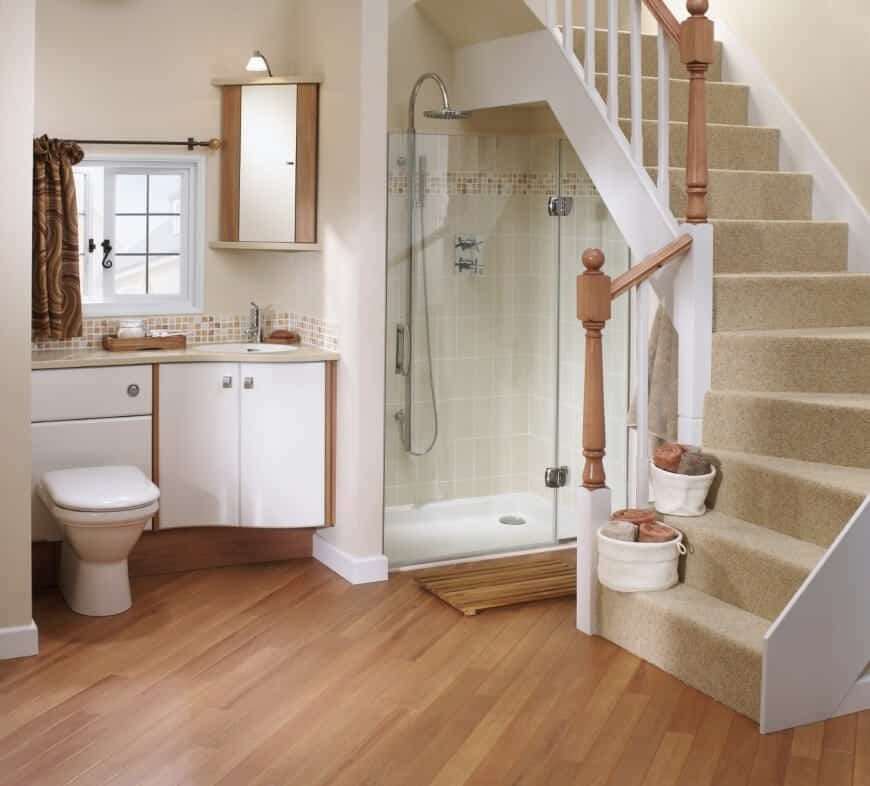This primary bathroom has a staircase leading to the home's main floor. It offers a floating vanity sink and a walk-in corner shower underneath the staircase.