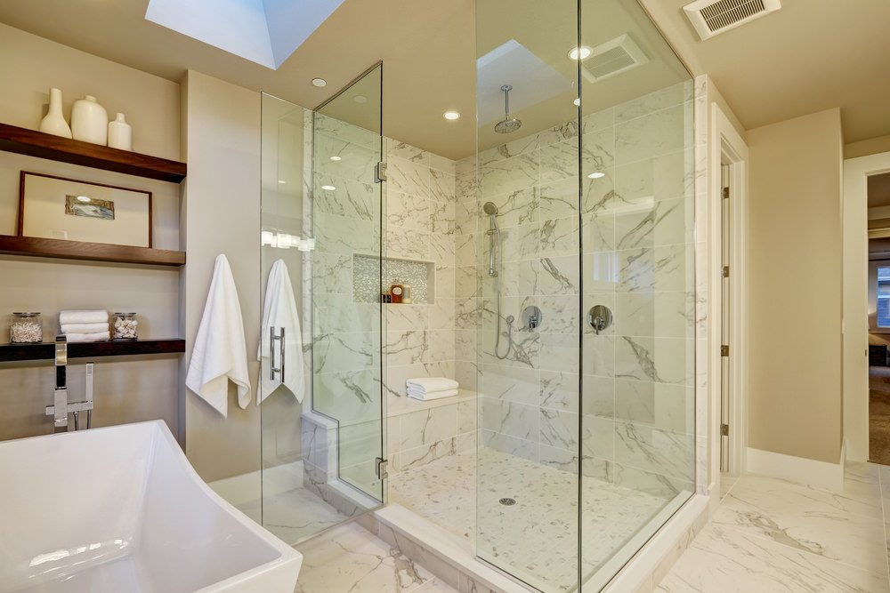 Primary bathroom featuring a freestanding tub along with a walk-in shower room. The room features built-in shelves and a skylight.