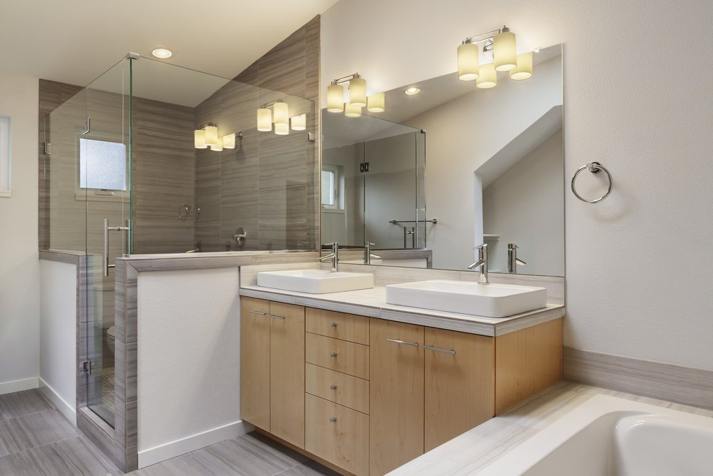Primary bathroom featuring a double sink lighted by wall lights, a walk-in corner shower and a drop-in soaking tub.