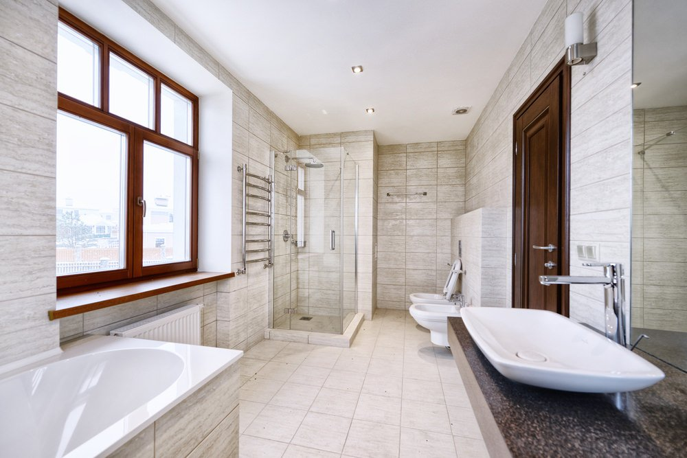 Primary bathroom featuring a walk-in shower, a drop-in soaking tub and a large vessel sink.