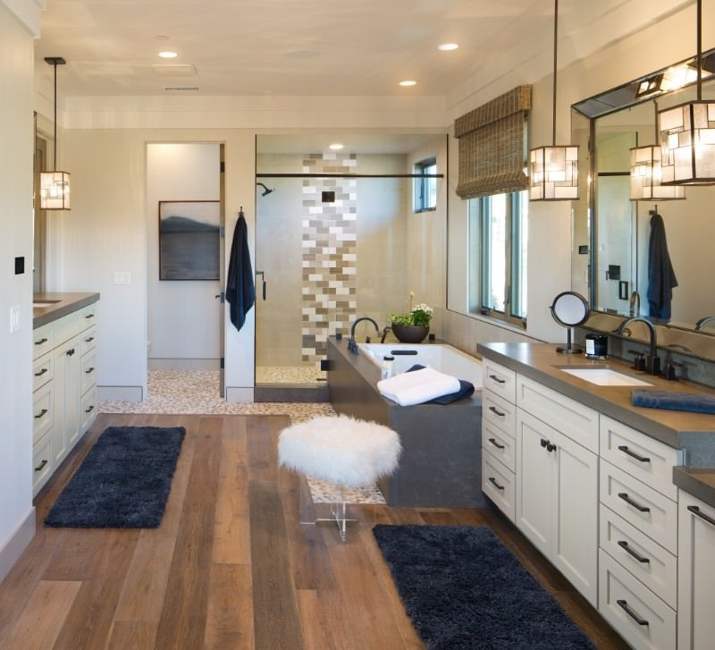 Primary bathroom with hardwood floors topped by area rugs. The bathroom offers a walk-in shower room and a drop-in deep soaking tub, along with two sink counters.