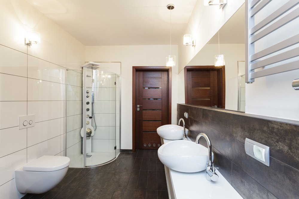 Primary bathroom with hardwood floors and tiles walls. It offers a walk-in shower booth and two vessel sinks on a floating vanity.