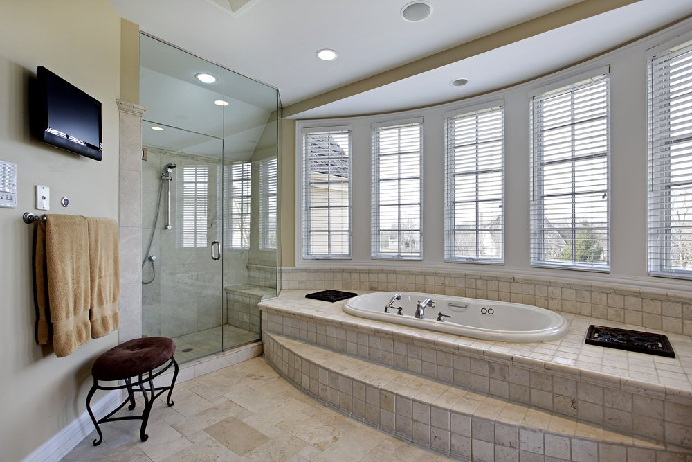 Primary bathroom featuring beige tiles flooring. It has a drop-in tub on a tiles platform and a walk-in corner shower, along with a TV on the wall.