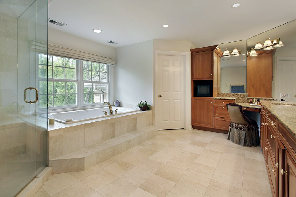 A spacious primary bathroom featuring beige tiles flooring. It offers a walk-in corner shower and a drop-in tub, along with a powder area.