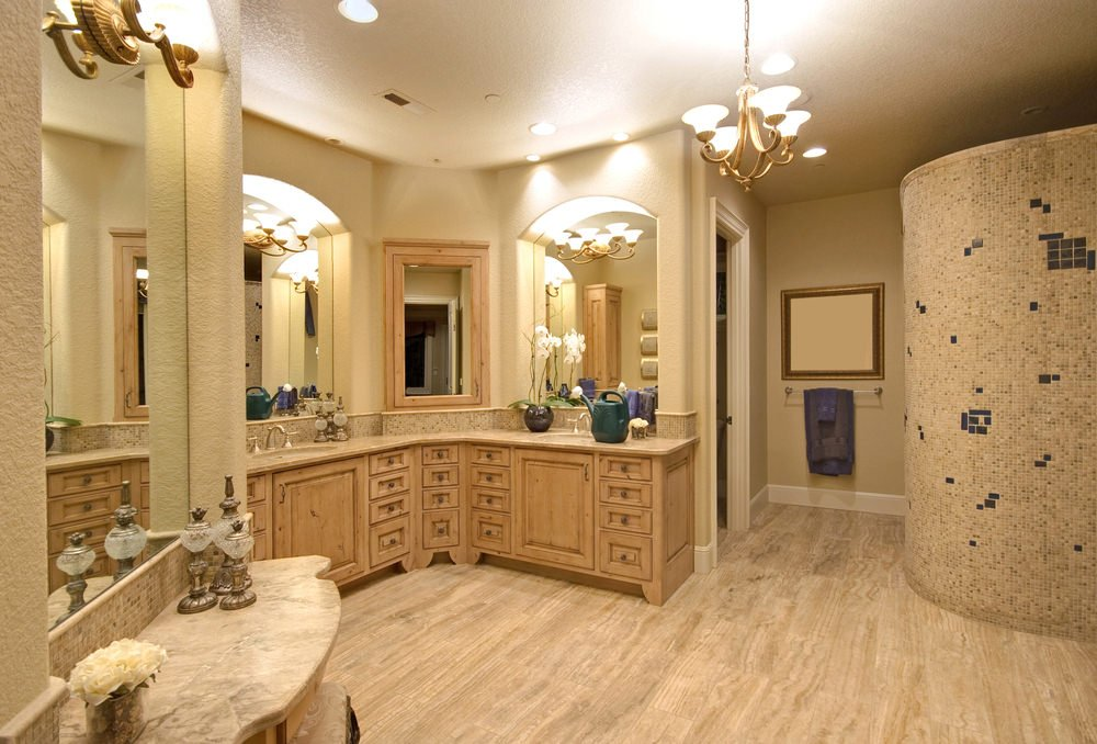 A spacious primary bathroom with hardwood floors and beige walls. The room offers two sinks along with a walk-in corner shower room.