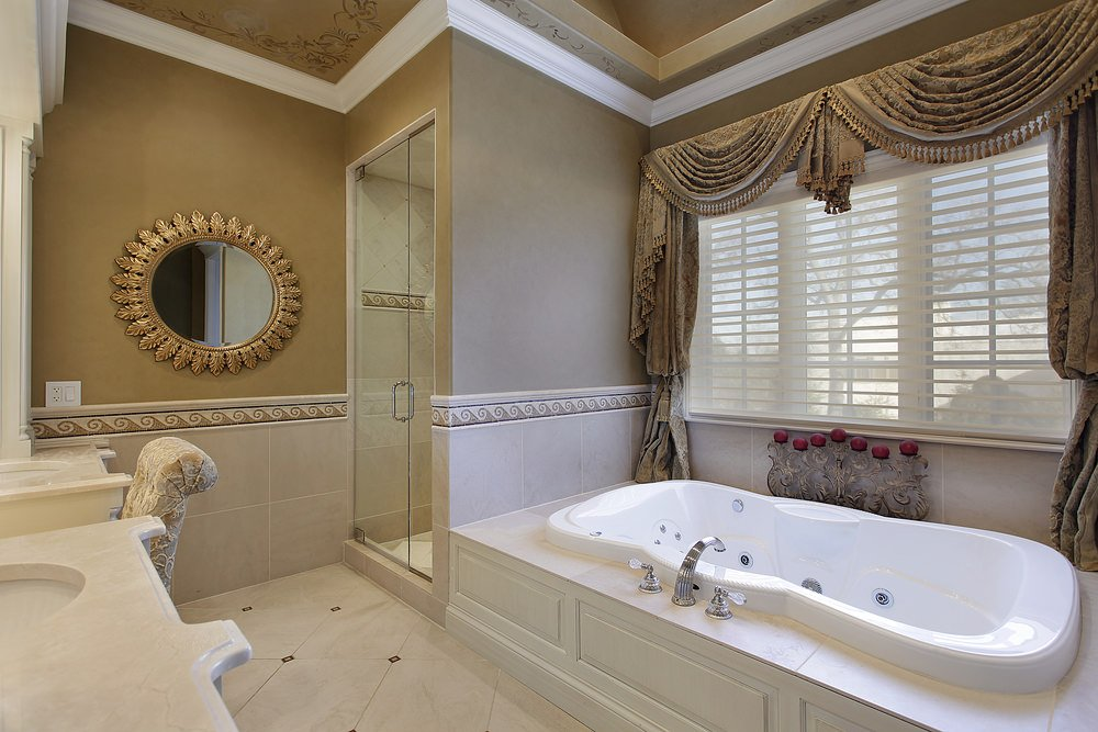 Primary bathroom with beige tiles floors, brown walls and elegantly decorated brown ceiling. It offers a powder desk in between two sinks, a drop-in tub and a walk-in corner shower room.