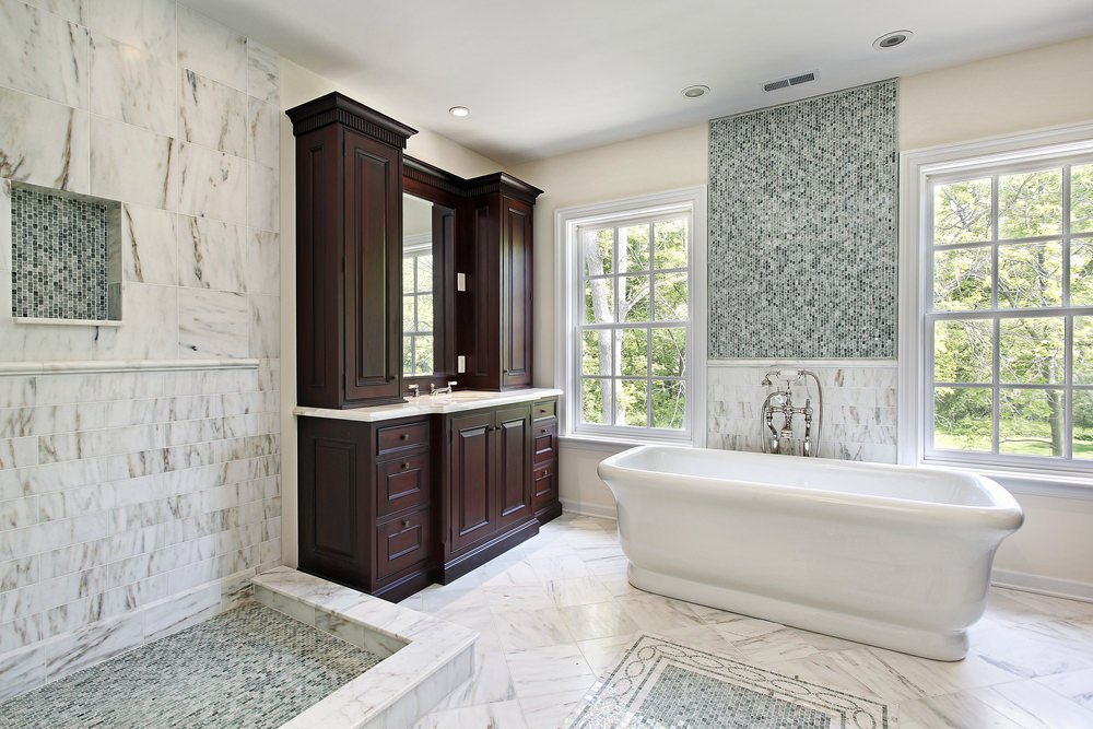 Primary bathroom with stylish marble tiles walls on the open shower and a freestanding tub, set on the marble tiles flooring.