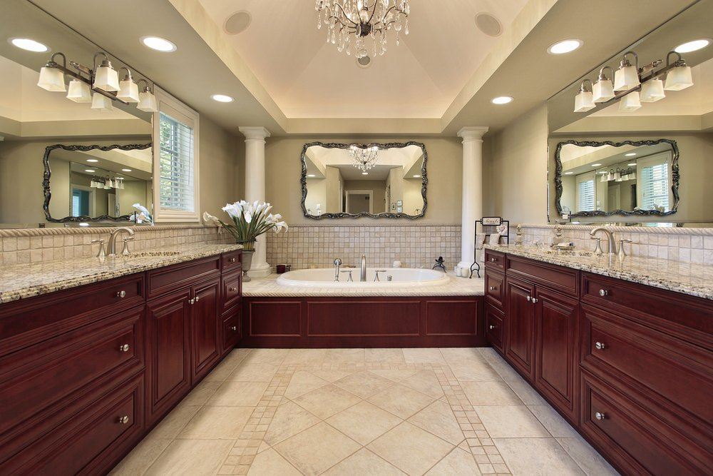 A spacious primary bathroom featuring two sink counters and a drop-in tub. The room features a tray ceiling lighted by a fancy chandelier, along with beige tiles flooring.