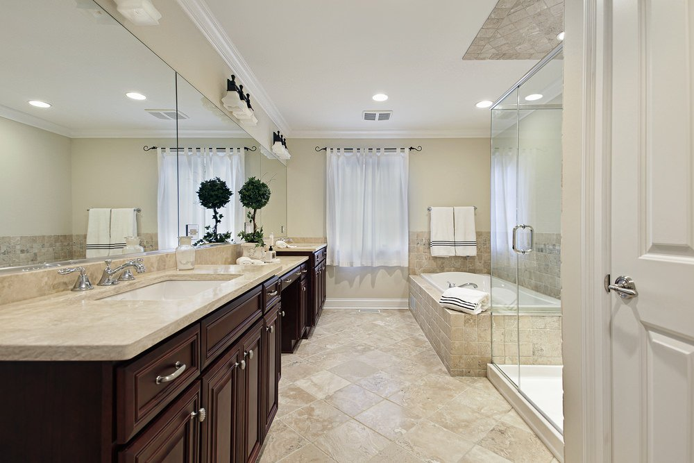 Large primary bathroom with beige tiles flooring. IT has a walk-in shower, a drop-in deep soaking tub and two sink counters with a powder desk in between.