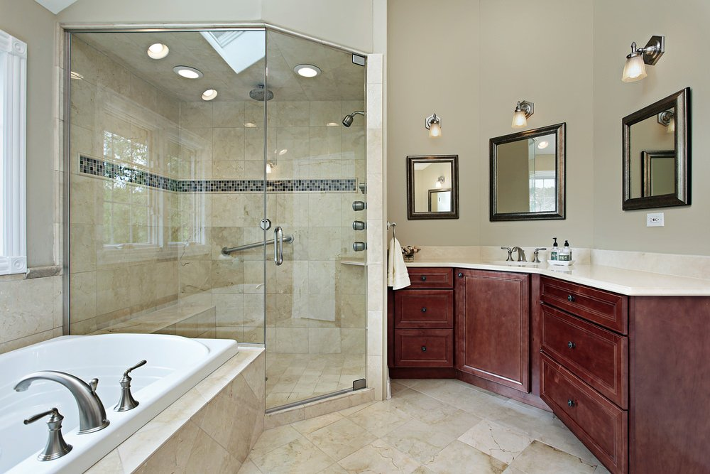 Primary bathroom featuring a walk-in corner shower, a curved sink counter lighted by wall lights and a drop-in tub.