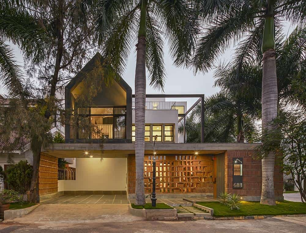 This is a front exterior view of the house with a alrge carport on one side topped with glass walls and large balconies. These are then complemented by the patterned red brick walls and tropical trees.