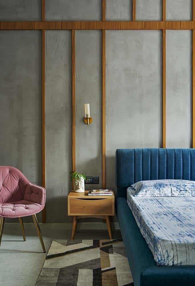 This is a close look at the primary bedroom with a large cushioned bed that has a blue tone to it that makes it stand out against the concrete wall behind with thin wooden accents that match the bedside table by the pink cushioned chair.