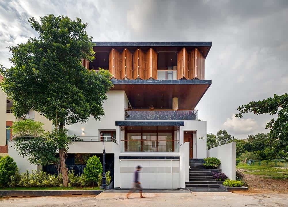 This is a front exterior view of the house with bright white exterior walls on the lower levels adorned by the tall tree and windows. On the upper levels are balconies and wooden folding panels that open to glass walls.