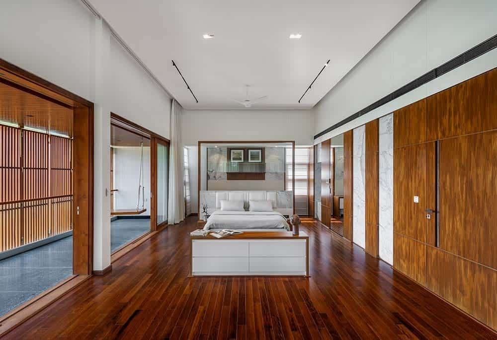 This is the spacious primary bedroom that has hardwood flooring and wooden doors as well as wooden slatted panels on the balcony. These make the bright white bed stand out on the far side with a glass wall behind it.