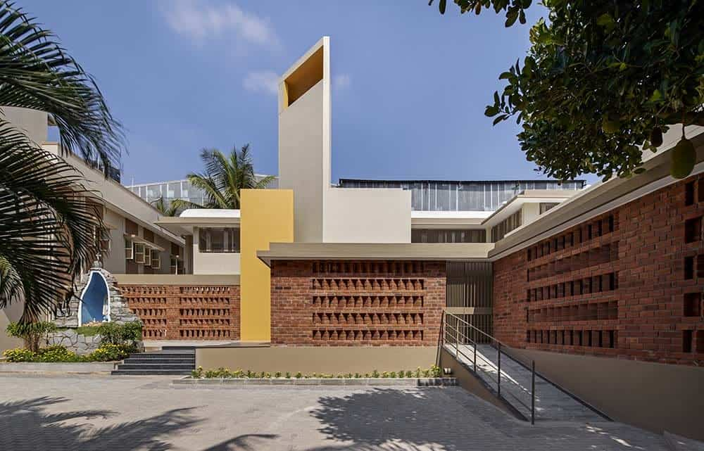 This is the a front view of the seminary with multiple concrete and colorful structures as well as concrete walkways and driveways complemented by the patterned red brick walls.