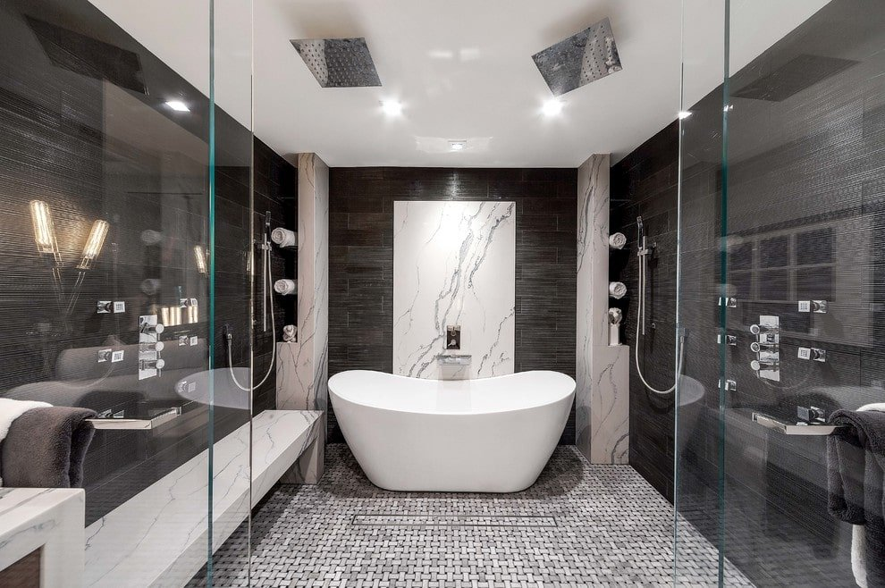 This master bathroom offers chrome dual shower heads and a tiled bench along with a freestanding tub situated in between the marble shelves.