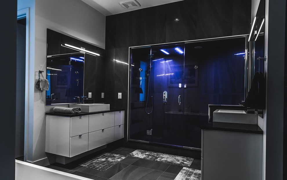 The black master bathroom showcases a walk-in shower accented with blue strip lights along with facing vessel sink vanities lighted by linear sconces that are mounted on the frameless mirrors.