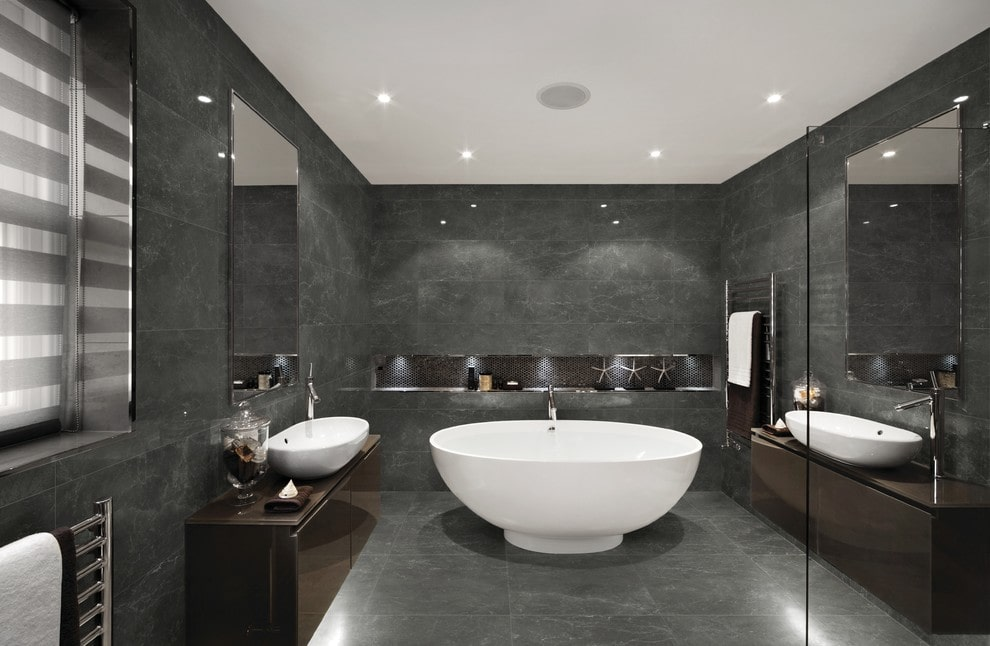 A freestanding tub matches the vessel sinks that sit on floating vanities. This room has black tiled flooring extending to the walls that are fitted with an inset shelf.