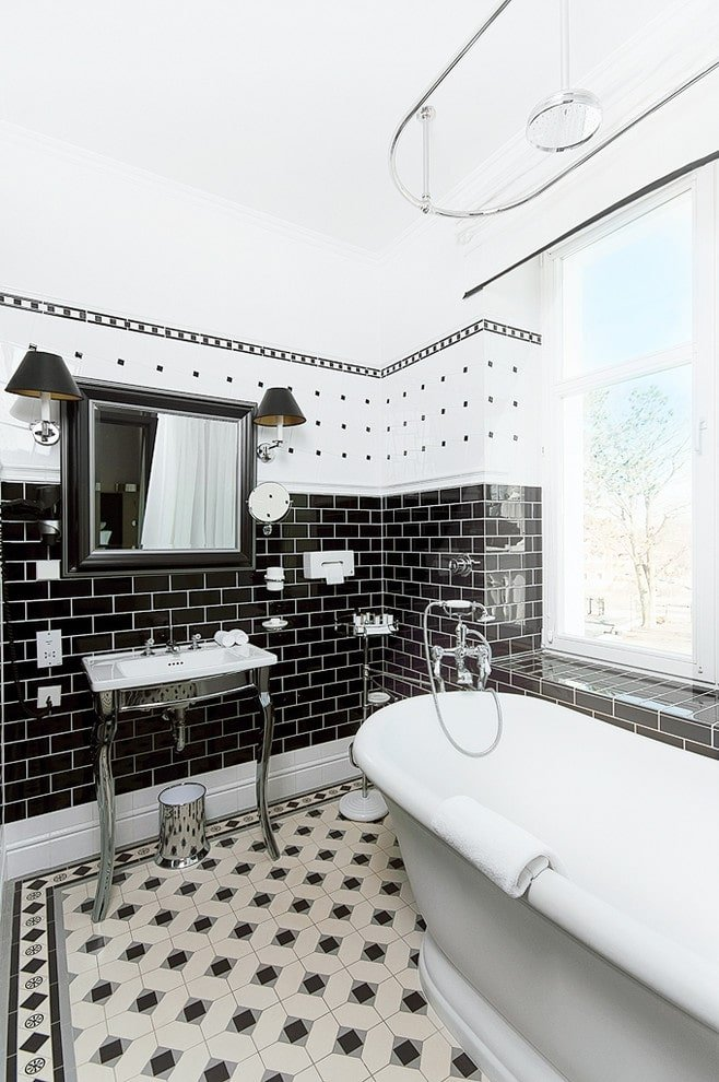 Traditional sconces flank a black framed mirror that hung above the sleek washstand with a matching bin underneath. It is accompanied by a freestanding tub under a chrome shower head.