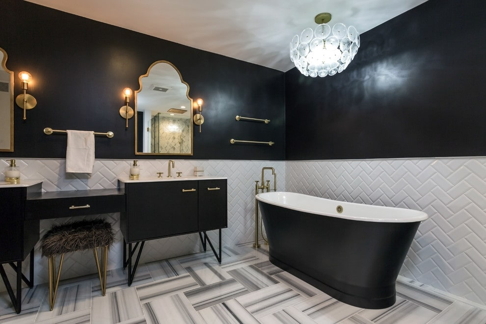 A faux fur stool sits at a dual sink vanity paired with gorgeous arched mirrors. There's a black freestanding tub on the side that's lighted by a brass chandelier.