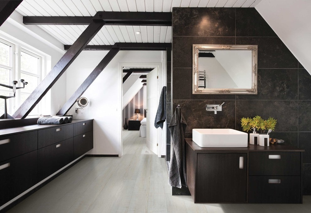 A white door opens to this master bathroom with dark wood storage cabinets and a floating vanity that's topped with a vessel sink. It includes a chrome framed mirror mounted on the black tiled wall.