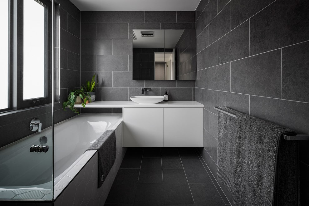 A mirrored medicine cabinet hangs above the white vessel sink vanity that's fixed against the black tiled walls. It is accompanied by a deep soaking tub underneath the glazed windows.
