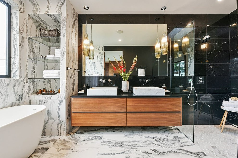 Inset marble shelf and white tiled flooring add a striking contrast to the black tiled walls that are mounted with chrome fixtures and a frameless mirror. This room has a walk-in shower and a bathtub along with a dual vessel sink vanity lighted by glass pendants.