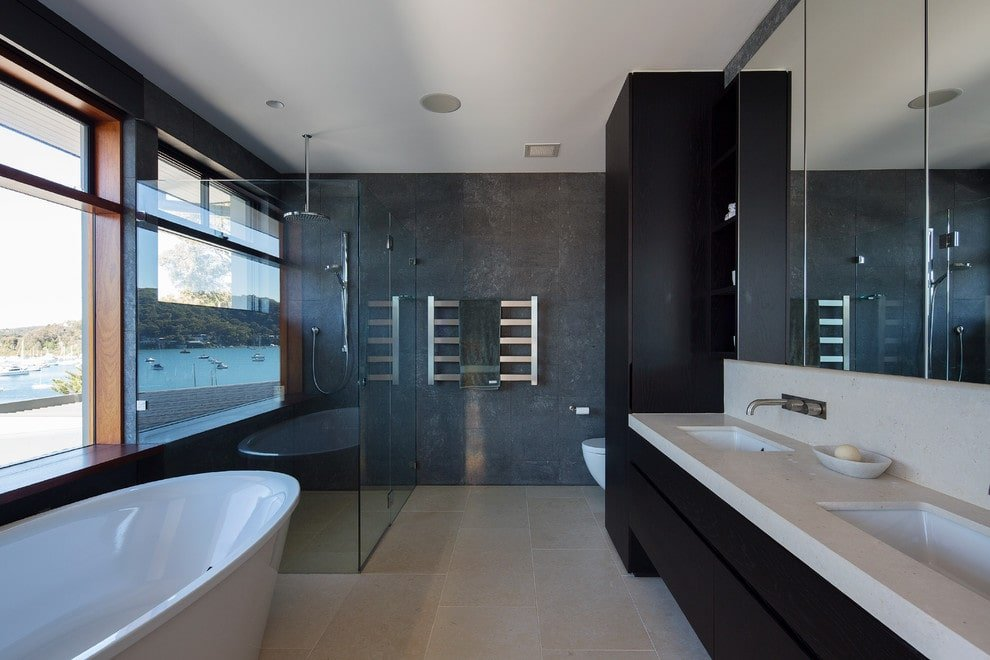 This master bathroom boasts a freestanding tub and a walk-in shower enclosed in frameless glass panels. It includes a chrome towel rack and a toilet concealed with the full height cabinet and dual sink vanity.