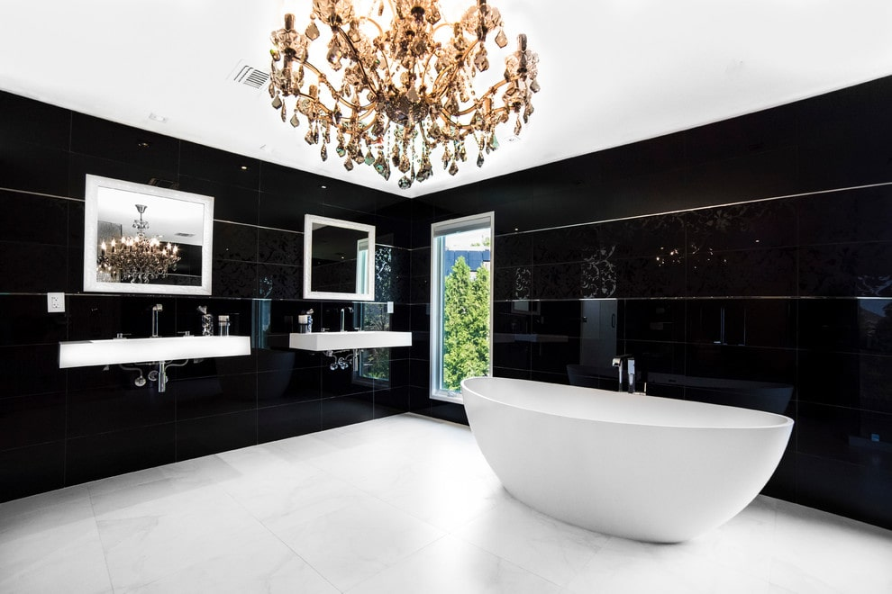 Minimalist master bathroom illuminated by a grand crystal chandelier along with natural light from the glazed windows. It has a freestanding tub and wall-mounted sinks paired with white framed mirrors.