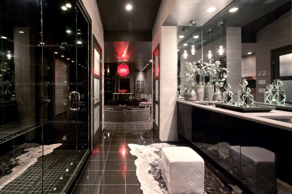 The luxury master bathroom features a walk-in shower and a high gloss vanity paired with a white cube ottoman that sits on a cowhide rug over black tiled flooring. There's a deep soaking tub at the far end lighted by a red crystal chandelier.