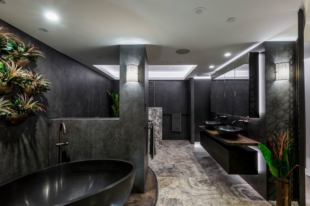 Fresh potted plants add life in this black master bathroom with a freestanding tub and a dual vessel sink vanity paired with mirrored medicine cabinets. It is illuminated by a wall sconce and recessed ceiling lights.