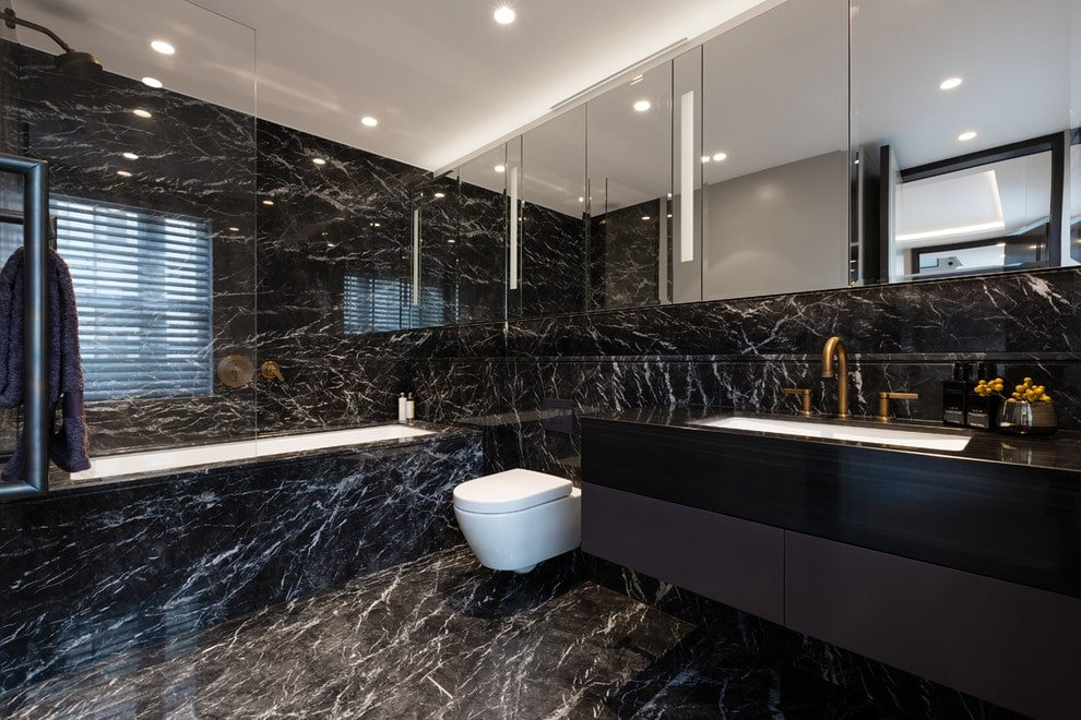 Trendy master bathroom with a wall hung toilet and a deep soaking tub matching with the black marble walls and flooring. It includes mirrored medicine cabinets and a floating sink vanity fitted with brass fixtures.