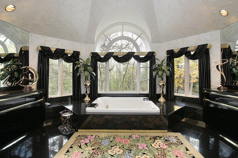 A charming floral rug stands out in this master bathroom with sleek sink vanities and a deep soaking tub by the glazed windows dressed in classy valances. It has black tiled flooring and a textured vaulted ceiling mounted with recessed lights.