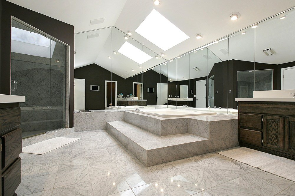 Spacious master bathroom with marble tiled flooring and a cathedral ceiling fitted with skylights and recessed lights. It includes dark wood vanities and a walk-in shower along with a drop-in tub by the mirrored walls creating a larger visual space in the room.