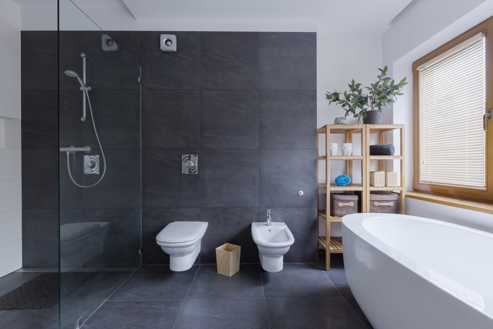 A green potted plant creates a refreshing ambiance in this master bathroom with a freestanding tub and wall hung toilets fixed next to the walk-in shower. It includes a glazed window and wooden shelving units over black tiled flooring extending to the backsplash.