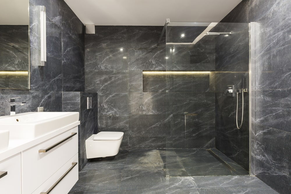 The sleek master bathroom features a floating sink vanity and a wall hung toilet facing the walk-in shower. It has black marble tiled flooring and walls fitted with an inset shelf.